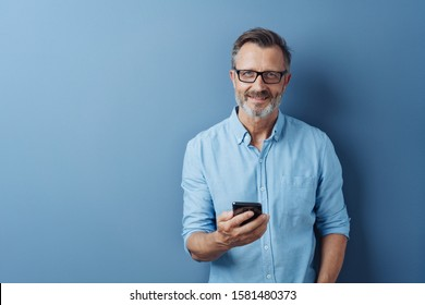 Smiling friendly man wearing glasses standing holding his mobile phone looking at the camera with a warm smile over a blue studio background with copy space