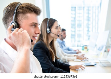 Smiling friendly man working in call center office with team as the customer care operators