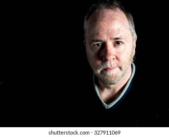 Smiling friendly middle aged man with beard stubble in black sweater on black background.