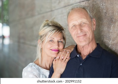 Smiling friendly middle-aged couple posing together alongside a wall looking at the camera