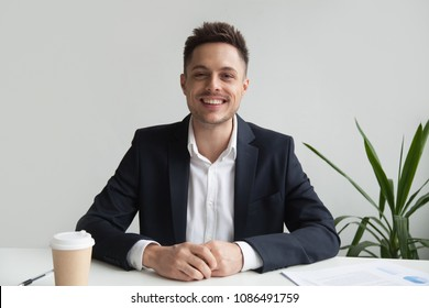 Smiling friendly millennial businessman in suit sitting at desk looking at camera, confident successful ceo, happy young professional, business coach or executive manager head shot portrait
