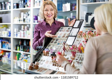 Smiling friendly positive seller helps customers choose cosmetics in store