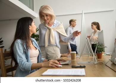 Smiling friendly senior female executive talking to asian employee working on pc, happy aged leader telling young coworker good news, excited older mentor supporting achievements of intern in office