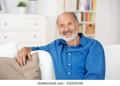 Smiling friendly senior man relaxing at home sitting on a sofa in his living room looking at the camera