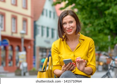 Smiling friendly stylish middle-aged woman in colorful yellow shirt using a mobile in town as she relaxes on a bench in a quiet street