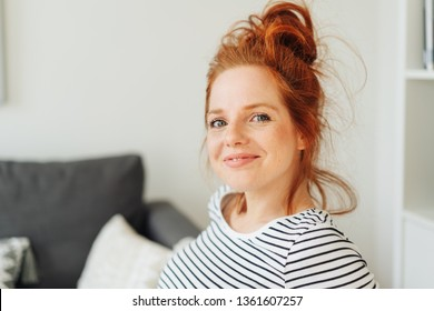 Smiling friendly young redhead woman looking at the camera with an impish grin as she relaxes at home on a sofa