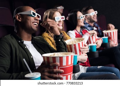 smiling friends in 3d glasses with popcorn and soda watching movie in cinema