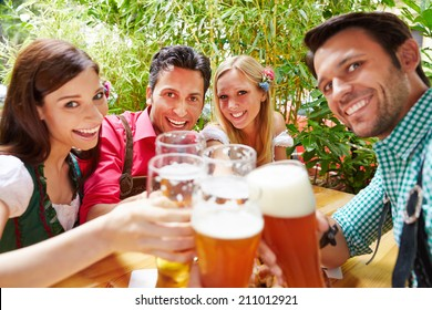 Smiling friends in beer garden clinking their glasses in summer