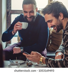 Smiling friends drinking coffee and looking at the mobile phone in a coffee shop