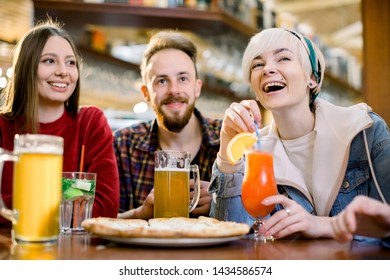 Smiling friends eating pizza and drinking juice, laughing and having fun in restaurant, diverse millennial colleagues enjoying lunch during work break sitting at coffee table in loft cafe