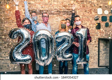 Smiling friends with face mask are celebrating new year's eve party in club in covid-19 time - Group of young people holding balloons looking at camera and smile wit eye all together throwing confetti - Shutterstock ID 1849354327