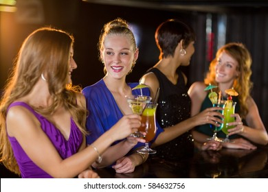 Smiling friends having glass of cocktail in bar