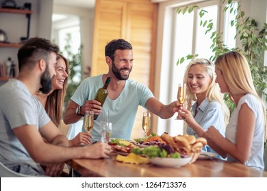 Smiling friends having lunch together at home.People,food and drink,fun and holidays concept