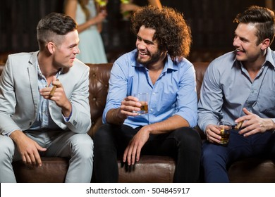 Smiling friends interacting with each other while having cigar and whisky in bar