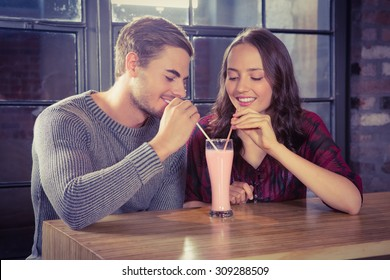 Smiling friends sharing smoothie at coffee shop