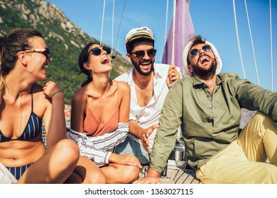 Smiling friends sitting on sailboat deck and having fun.Vacation, travel, sea, friendship and people concept