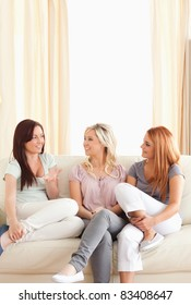 Smiling friends sitting on a sofa in a living room
