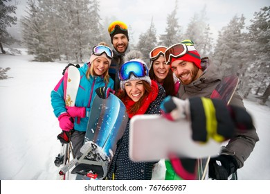 smiling friends with ski on winter holidays - Skiers having fun on the snow and making selfie