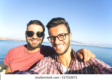 Smiling friends taking a self portrait with smart phone in a summer day - City and sea in background - Concept about friendship and people
