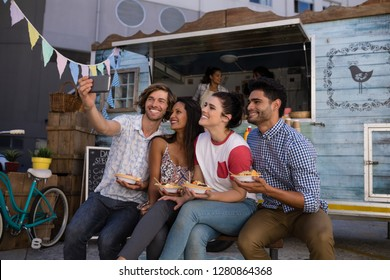 Smiling friends taking selfie from mobile phone