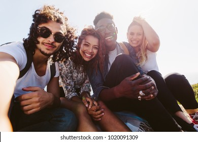 Smiling friends taking selfie on a holiday. Group of men and women sitting together outdoors on a summer day making self portrait.