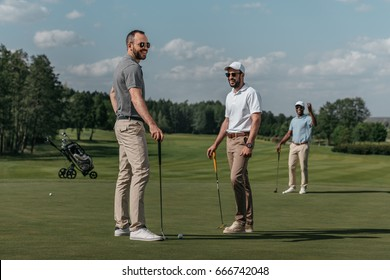 smiling friends talking while playing golf together on green at daytime