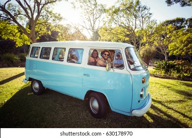 Smiling friends travelling in campervan