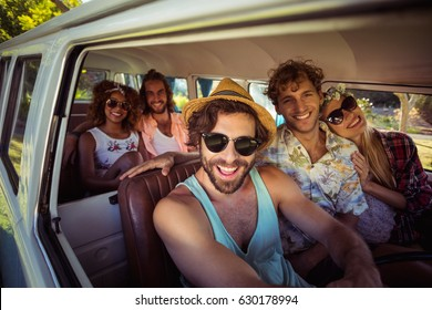 Smiling friends travelling in campervan