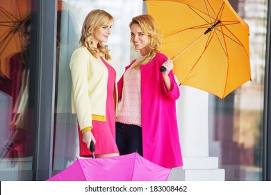 Smiling friends with umbrellas