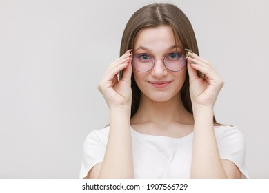 smiling frowning office girl staring at camera through eyeglasses on white background. Young woman adjusting eyewear. Glasses wearing concept.