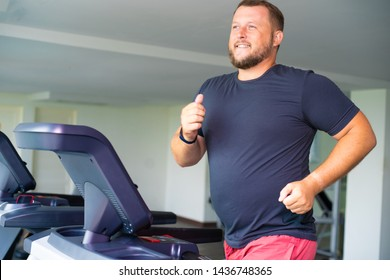 smiling full male runs on a treadmill in a gym. concept of weight loss and sport. side view