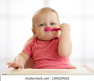 smiling funny baby eating healthy food alone