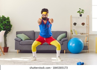 Smiling funny bearded man in multicolored sport clothes and glasses doing exercise during training at home over room interior. Active lifestyle, funny sport, workout, training at home concept
