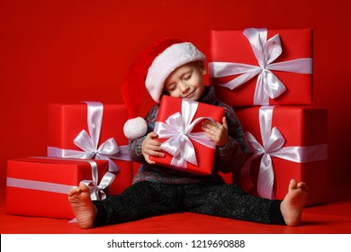 Smiling funny child boy in Santa red hat fell asleep with Christmas gifts in hand in hand on red background. Christmas concept.