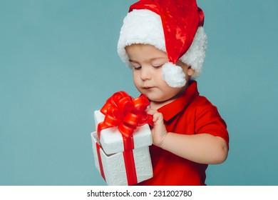Smiling funny child (kid, boy) in Santa red hat. Holding Christmas gift in hand. Christmas concept. Shooting on blue background