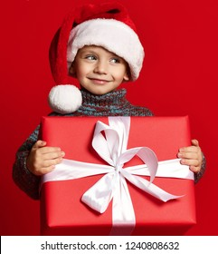 f714ea9478b7b Smiling funny child in Santa red hat holding Christmas gift in hand over red  wall background