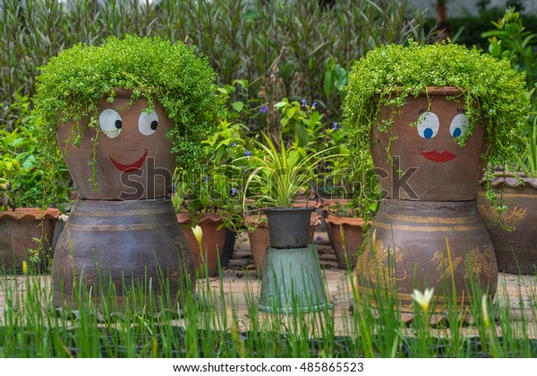 Smiling funny flower pots in a garden.