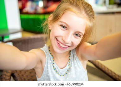 smiling funny little girl with freckles doing selfie