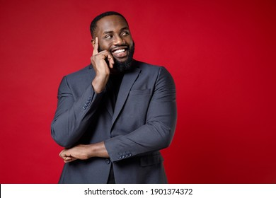 Smiling funny pensive young african american business man 20s wearing classic jacket suit standing put hand prop up on chin looking aside isolated on bright red color wall background studio portrait