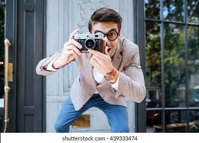 Smiling funny photographer in round glasses using old camera and taking photos outdoors