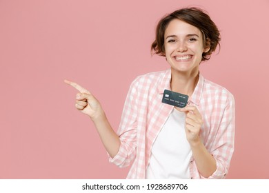 Smiling funny young brunette woman 20s wearing casual checkered shirt standing hold in hand credit bank card pointing index finger aside isolated on pastel pink colour background, studio portrait