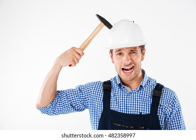 Smiling funny young builder applying hummer to his head in helmet and having fun isolated on a white background