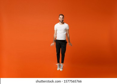 Smiling funny young man in casual white t-shirt posing isolated on bright orange wall background studio portrait. People lifestyle concept. Mock up copy space. Having fun, fooling around, jumping