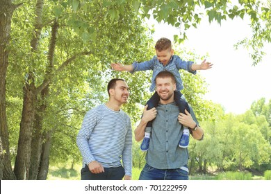 Smiling gay couple with son in park