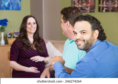Smiling gay man and partner with surrogate mother