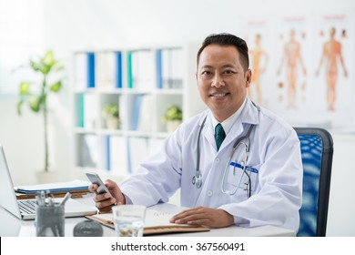Smiling general practitioner with smartphone in his hand looking at camera