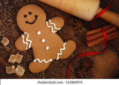 Smiling gingerbread man with sugar, spices, and vintage rolling pin on rustic, dark wood background.  Low key still life with directional, natural lighting for effect.