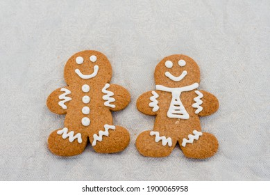 Smiling gingerbread man with sugar, spices, and vintage rolling pin on rustic, textile linen background. Top view still life with natural light.