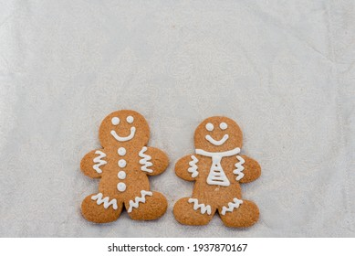 Smiling gingerbread man with sugar, spices, and vintage rolling pin on rustic, textile linen background.