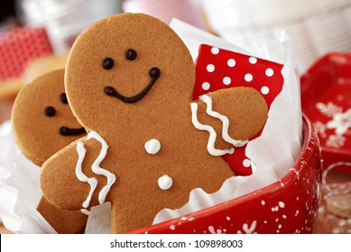 Smiling gingerbread men nestled in holiday dish with gift-wrapped surprise.  Baking ingredients and supplies (including baker's twine and rolling pin) in background.  Macro with extremely shallow dof.